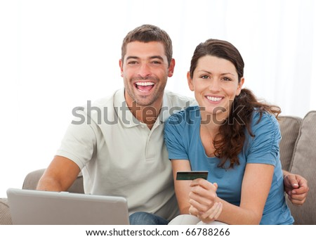 Cute couple with their laptop and credit card sitting in the living room at home - stock photo