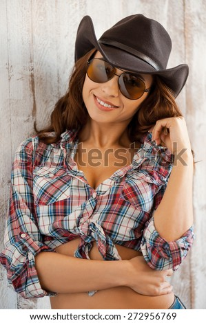 Cute cowgirl. Beautiful young cowgirl posing while standing against thewooden background - stock photo