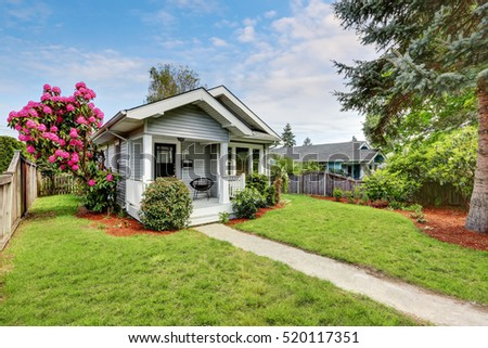 cute craftsman home exterior with green grass and blooming tree northwest usa