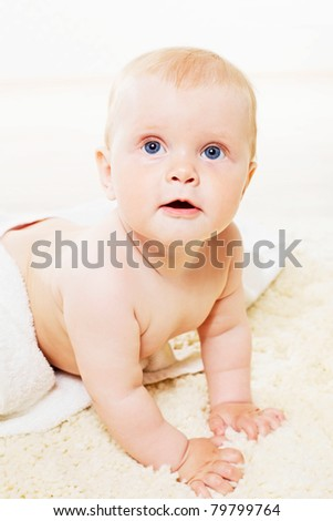 Cute curious baby with blue eyes looking out from towels