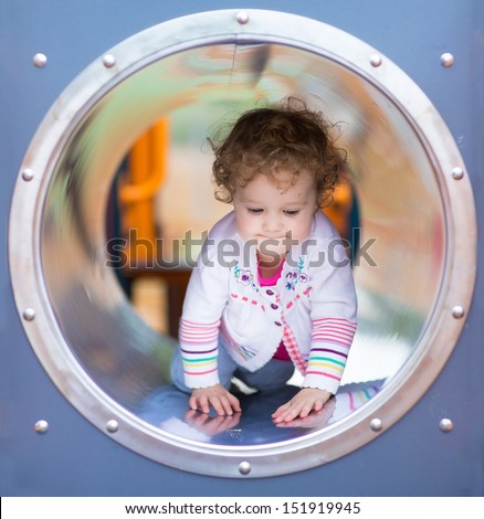 Cute curly baby girl climbing a slide on a playground - stock photo
