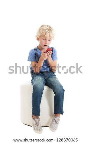 Cute curly blond boy wearing a blue shirt, suspenders and jeans, sitting on a white chair and plays with a red mobile phone. Studio shot, isolated on white background. - stock photo