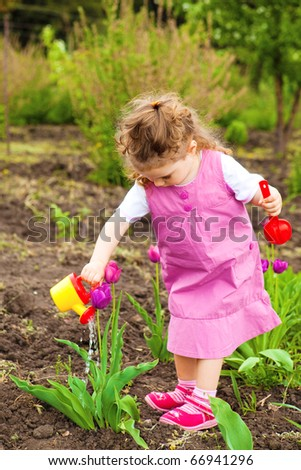 Cute curly girl watering tulips in the garden - stock photo