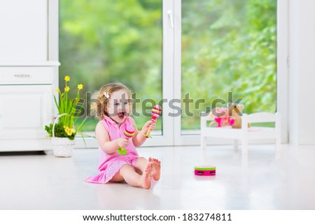Cute curly laughing toddler girl in a pink dress playing tambourine and maracas in a sunny room with a big garden view window with a toy bed and spring flowers next to her, white modern interior home - stock photo