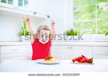 Cute curly laughing toddler girl in a red shirt playing with fork and spoon eating spaghetti with tomato sauce and vegetables for healthy lunch sitting in a white sunny modern kitchen with big window  - stock photo
