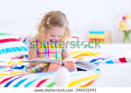 Cute curly little toddler girl reading a book sitting in a sunny bedroom on a wooden white bed with colorful rainbow bedding enjoying a nice weekend morning - stock photo