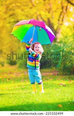 Cute curly toddler girl in yellow waterproof coat and boots holding colorful umbrella playing in the garden by rain and sun weather on a warm autumn or summer day - stock photo