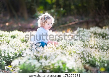 Cute curly toddler girl playing with first spring flowers in a beautiful spring sunny park - stock photo