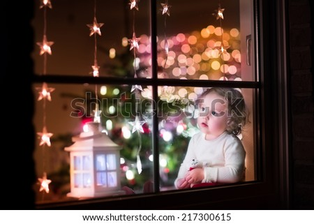 Cute curly toddler girl sitting with a toy bear at home during Christmas time, preparing to celebrate Xmas Eve, view through a window from outside into a decorated dining room with tree and lights  - stock photo
