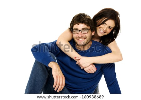 Cute dark haired couple cuddling smiling at the camera isolated on a white background