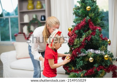 Cute daughter and mother celebrating christmas at home in the living room - stock photo