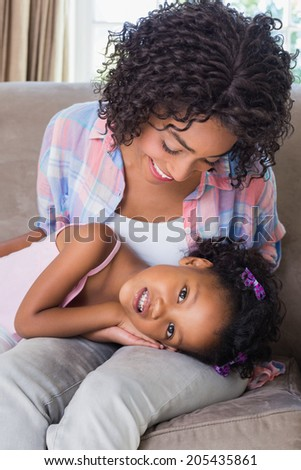 Cute daughter lying across mothers lap at home in the living room - stock photo