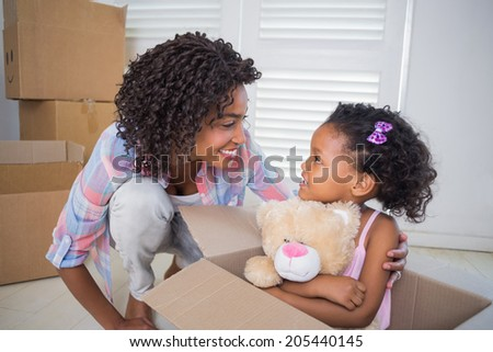 Cute daughter sitting in moving box holding teddy with mother at home in the living room - stock photo