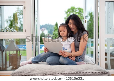 Cute daughter sitting on her mother's lap with laptop - stock photo