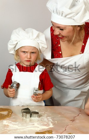 cute daughter with mother in white aprons on kitchen - stock photo