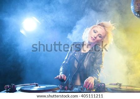Cute dj woman having fun playing music on vinyl record deck - stock photo