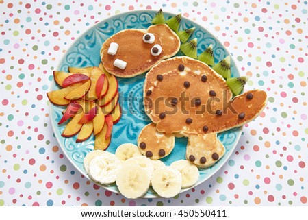 Cute dragon shaped pancakes with peaches, banana and kiwi - stock photo
