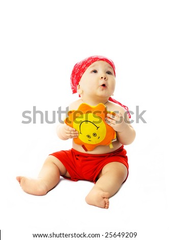 cute dreamy ten months old baby wearing summer clothes with a toy Sun in his hands - stock photo