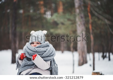 cute dreamy toddler girl in oversize knitted scarf and red gloves in winter snowy forest - stock photo