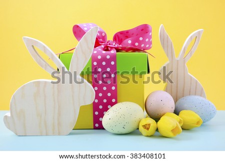 Cute Easter Bunny with bright color gift box on yellow and blue background.  - stock photo