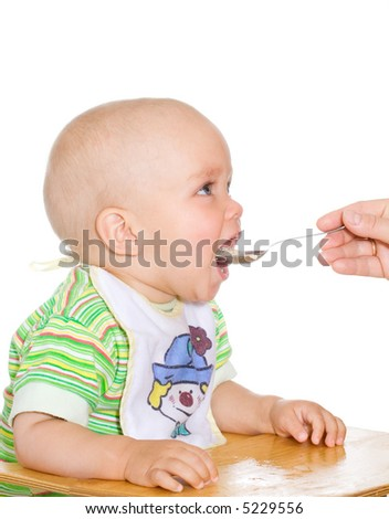 Cute eating child and spoon. Isolated over white - stock photo