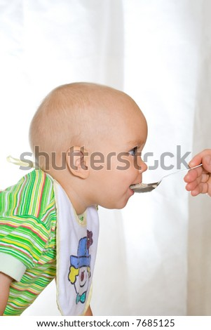 Cute eating child with spoon. At window background - stock photo