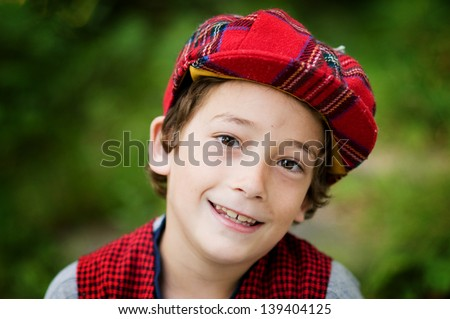 cute eight year old boy wearing a plaid Scottish cap