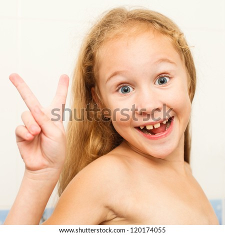 Cute eight year old girl in a victory pose in bathroom. The symbol of purity and hygiene education.
