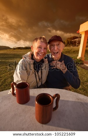 Cute elderly couple at table in a field - stock photo