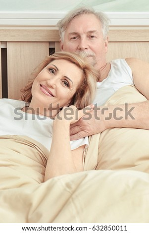 Cute elderly couple resting in bed at home