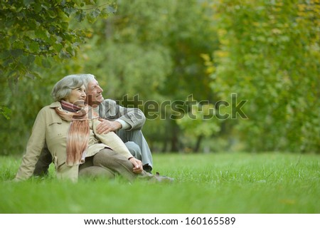 Cute elderly couple walking in the park in September - stock photo