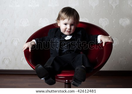 cute elegant baby boy sitting on the red armchair - stock photo