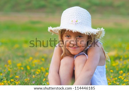 Cute elegant little girl sitting on the meadow on beautiful spring day. - stock photo