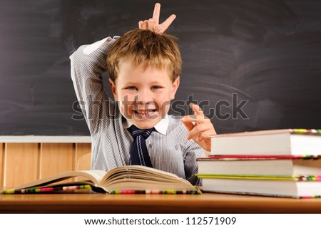 Cute elementary aged boy fooling at the lesson - stock photo