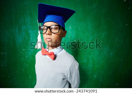 Cute elementary pupil in eyeglasses and graduation hat looking at camera - stock photo