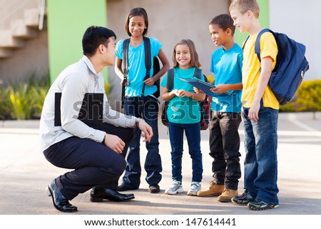 cute elementary pupils outside classroom talking to teacher - stock photo