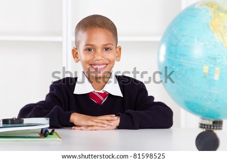 cute elementary schoolboy in classroom - stock photo
