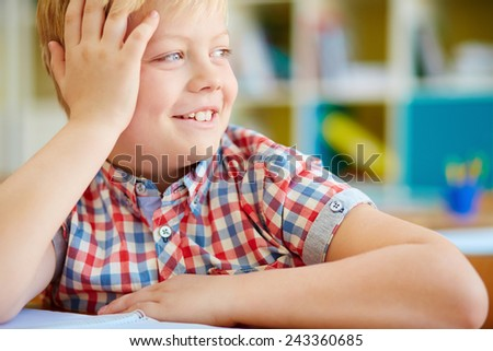 Cute elementary schoolboy looking aside with smile - stock photo