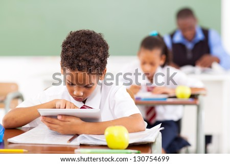cute elementary schoolboy using a tablet computer in classroom - stock photo