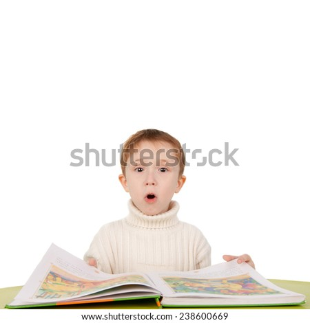 cute emotional boy surprising while reading a book - stock photo