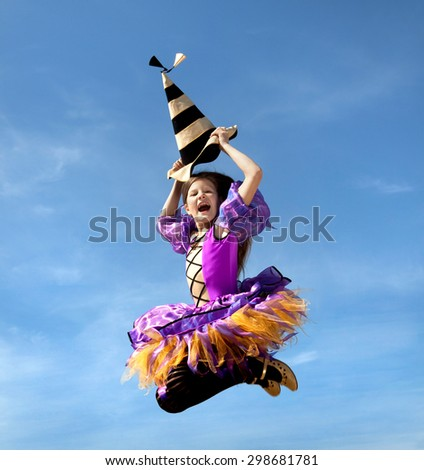 Cute Emotional Little Girl in a Costume of Witch Jumping at the Blue Sky. - stock photo