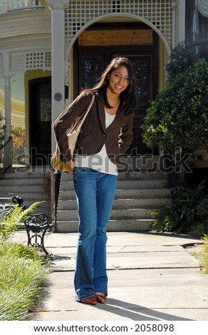 Cute ethnic girl in front of house