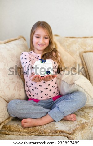Cute european toddler girl sitting in on sofa holding in her hands porcelain toy house with purple flower on roof