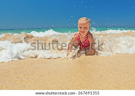 Cute excited girl crawling and having fun in sea waves  on the sand beach, summer vacation in the tropical island Bali - stock photo