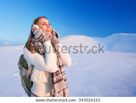 Cute excited girl holding head by hands with wonder looking up, enjoying beautiful winter mountains view, happy active wintertime holidays - stock photo