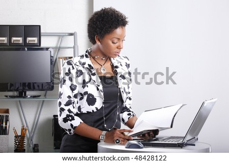 Cute executive interacts with her computer - stock photo