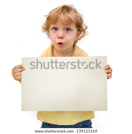 Cute fair-haired kid with blue eyes holding a blank sheet of paper making  funny face expression  isolated on white background - stock photo