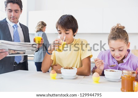 Cute family at breakfast time in kitchen - stock photo