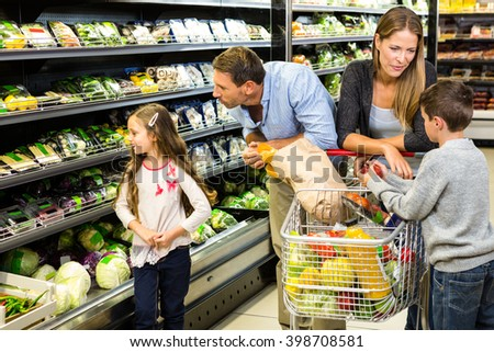 Cute family choosing groceries together in the supermarket - stock photo