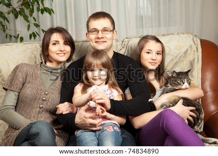 Cute family of four on their sofa at home - stock photo